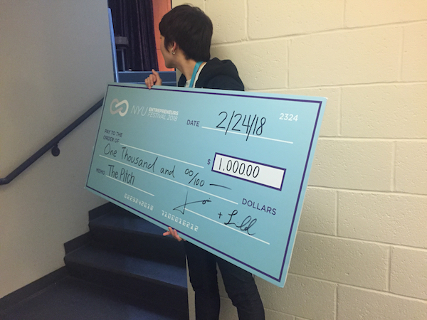 Image of Louise holding a large, fake check for $1,000, for the winners of the pitch competition at the 2018 Entrepreneurs Festival.