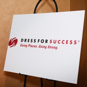Photo of a poster in a meeting room with the Dress for Success logo.