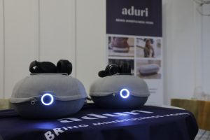 Photo of the Aduri cushion, turned on and with headphones