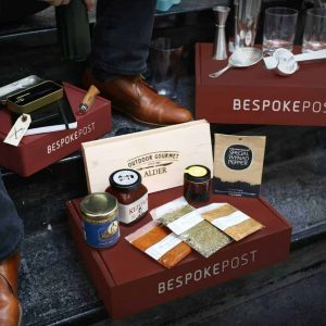Bespoke Post box on stairs with contents on top, a variety of luxury items like socks, bitters, body products, etc.