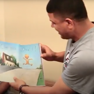 Black man reading to children