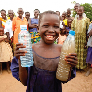 African child holding bottles of water from Charity Water