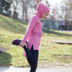 a woman wearing a sukoon athletic hijab while stretching