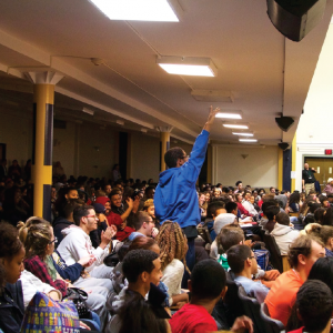 a crowded high school auditorium with one student standing up with hands raised